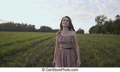 Young happy girl walking in green field.