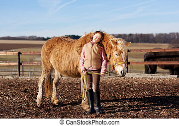 Young happy girl with her horse on the paddock on a sunny...