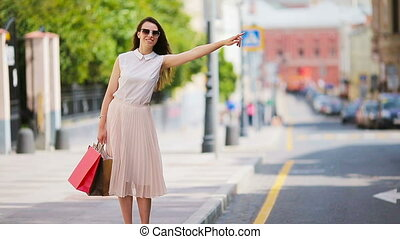 Young happy girl with shopping bags catch a taxi.