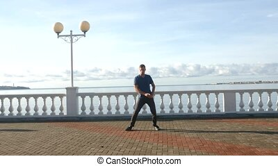 Young happy guy dancing on the waterfront against the sea....