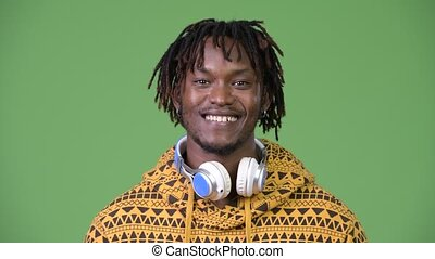 Young happy handsome African man smiling while wearing headphones