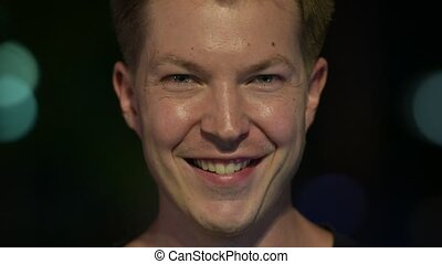 Young happy handsome Scandinavian man smiling outdoors at night