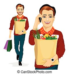 hipster man carrying grocery paper bag full of healthy food while talking on the mobile phone