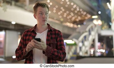 Young Happy Hipster Man Thinking And Using Phone In The City At Night