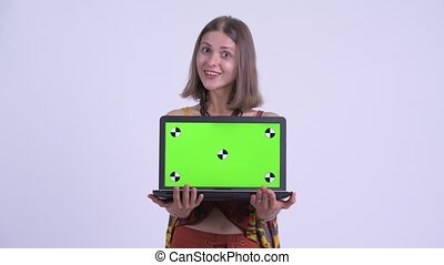 Young happy hipster woman showing laptop and looking...