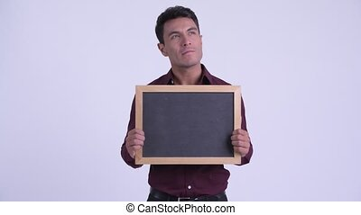 Young happy Hispanic businessman thinking while holding blackboard