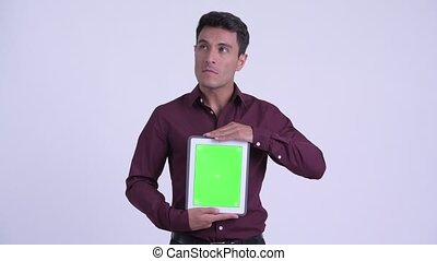 Young happy Hispanic businessman thinking while showing digital tablet