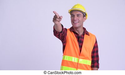Young happy Hispanic man construction worker directing and...