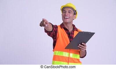 Young happy Hispanic man construction worker reading on...