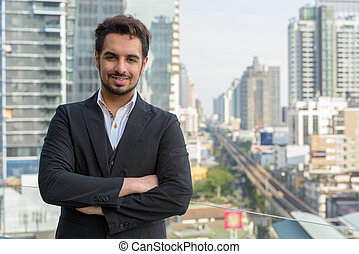 Young happy Indian businessman smiling with arms crossed at roof