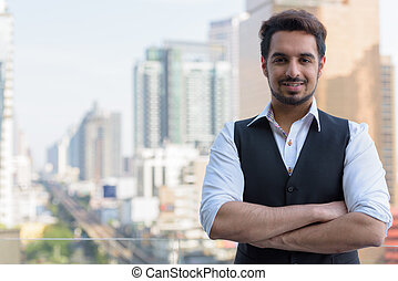 Young happy Indian man smiling with arms crossed at rooftop in B