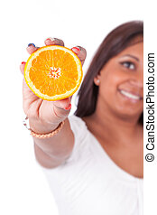 Young happy indian woman holding an orange slice