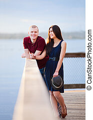 Young happy interracial couple standing together on wooden pier overlooking lake