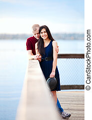Young happy interracial couple standing together on wooden pier overlooking lake. Man bowing head in prayer.