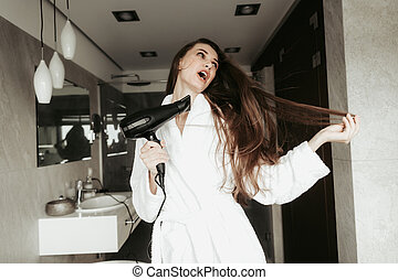 Young happy lady drying hair with blowdryer