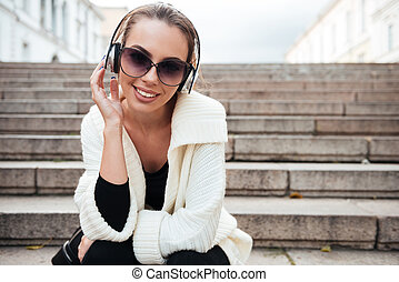 Young happy lady sitting on steps outdoors listening music
