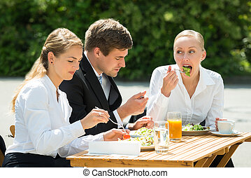 Businesspeople Eating Food In Restaurant