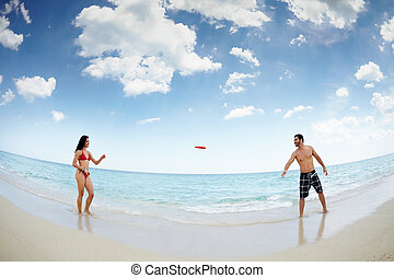 young happy man and woman playing with frisbee - boyfriend...