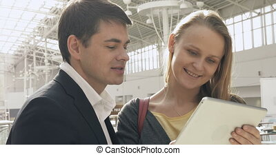 Young happy man and woman talking on business with pad