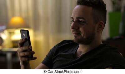 Young, happy man chatting on smartphone at home by night