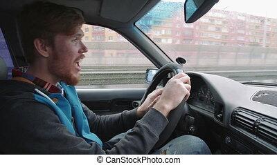 Young happy man driving a car dancing. Inside shot