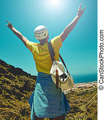 Young happy man in stylish clothes on top of the mountain reaches for the sun and showing rock and roll sign