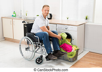 Man On Wheelchair Putting Clothes Into The Washing Machine...