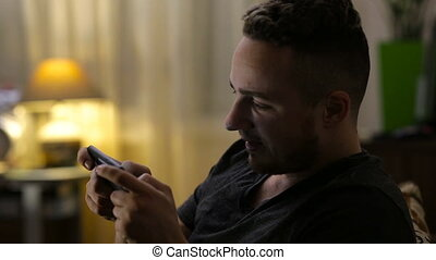 Young happy man playing game on smartphone at home