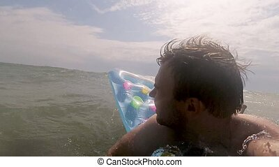 Young Happy Man Relaxing on Inflatable Mattress in Sea