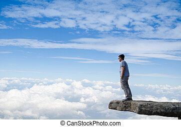 Young happy man standing on cliff's edge