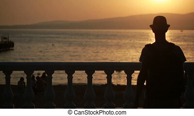 Young happy man using smartphone by the sea. tourist walks along the promenade