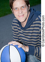 Young happy man with basketball