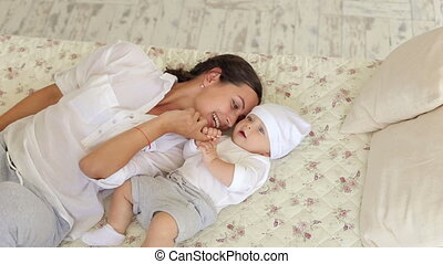 Young happy mom is playing with a newborn baby in the bedroom on the bed.