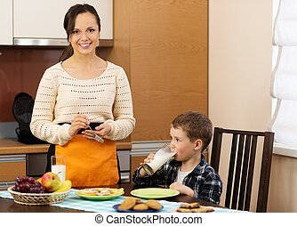 Young happy mother and her child eating healthy breakfast