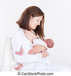 Young happy mother breastfeeding her newborn baby
