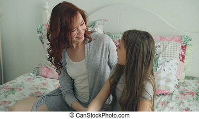 Young happy mother giving gift box to her little cute daughter celebrating birthday sitting on bed in cozy bedroom at home