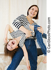Young happy mother having fun with her cute little baby holding her upside down