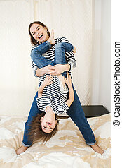 Young happy mother having fun with her cute little baby holding her upside down, playing