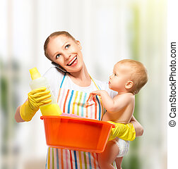 young happy mother is a housewife with a baby does homework...