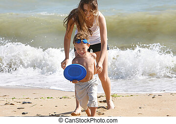 young happy mother playing with son on beach