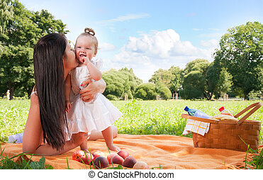 Young happy mother with daughter in park on picnic