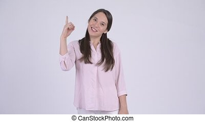 Young happy multi-ethnic businesswoman pointing up - Studio...
