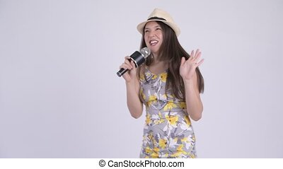 Young happy multi-ethnic tourist woman singing with microphone
