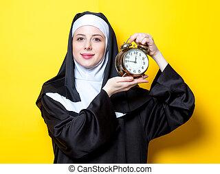 Young happy nun with alarm clock