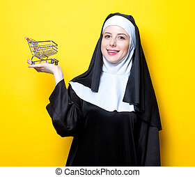 Young happy nun with shopping basket cart