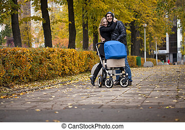 Young happy parents walking in autumn park