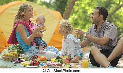 Young happy parents with two charming little girls on a picnic with fruits