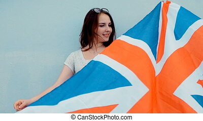 Young happy patriot girl holding the Great Britain, Union Jack flag