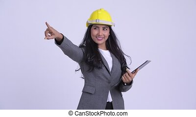 Young happy Persian businesswoman as engineer directing...