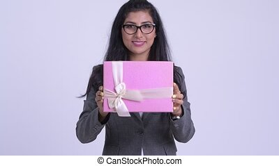 Young happy Persian businesswoman giving gift box - Studio...